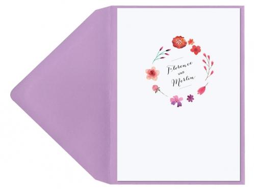 Hochzeitseinladungen mit Blumenkranz in Aquarellfarben und violettem Umschlag.