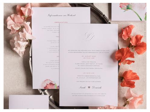 Hochwertige Hochzeitseinladung mit Blindprägung der Initialen und silber geprägten Herzen auf der Einladung und Umschlagsspitze.