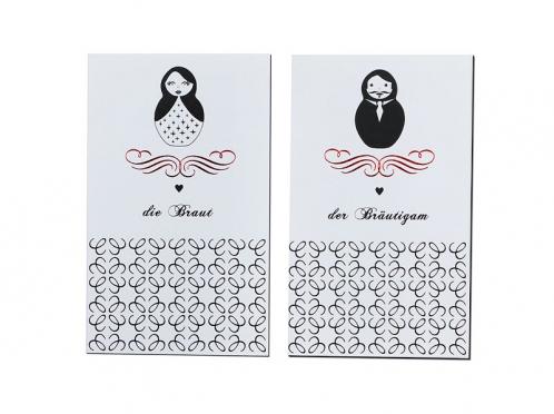 Personalisierte Tischkarten mit Matroschkas und roter Heißfolienprägung.