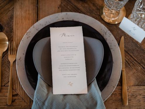 Stilvolle Menükarten zur Hochzeit mit goldenem Zweig.