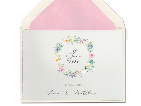 Zarte Pastellblumen in Aquarell zu einem natürlichen Blumenkranz geflochten. Save-the-Date Karte gedruckt auf Büttenpapier.