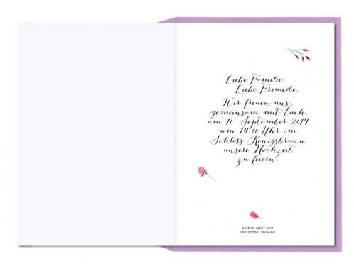 Einladungskarten mit Blumenkranz in Aquarellfarben und lila Briefumschlag.