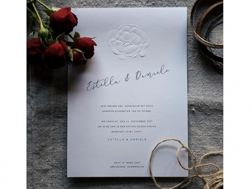 Einladungskarten mit von Hand geprägter Blüte und kalligrafischer Schrift.