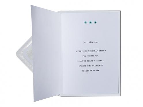 Save-the-Date Karte mit Blumenmuster und silber gefüttertem Briefumschlag.