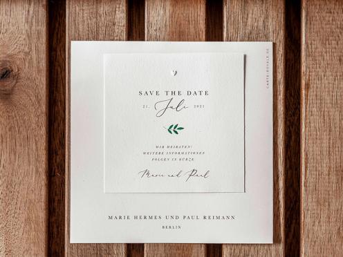 Save-the-Date-Karte mit Ruscus und Prägung gedruckt auf quadratischem Format.