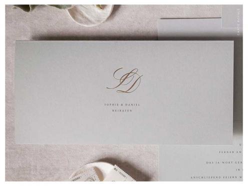 Hochzeitseinladung mit goldenen Initialen auf hochwertigem Papier in edlem Grau. Briefkuvert mit gold geprägtem Herz.