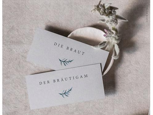 Tischkarten gedruckt auf grauem Premium Papier mit kleinem in Aquarell gezeichnetem Zweig.