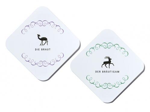 Tischkarten mit abgerundeten Ecken. Grün für die Herren und lila für die Damen.