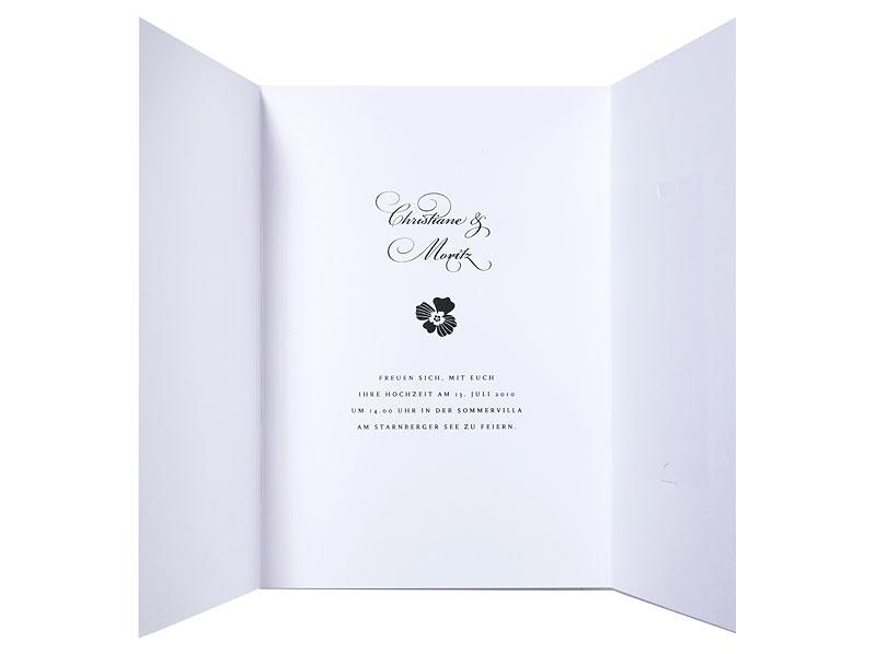 Hochzeitseinladungen als Altarfalz mit kleiner Blüte und kalligrafischer Schrift.