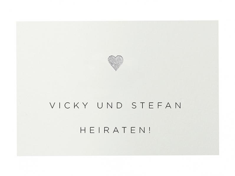 Heiraten im Herbst mit einer Einladung mit gemaltem Kastanienblatt und silber geprägtem Herz.