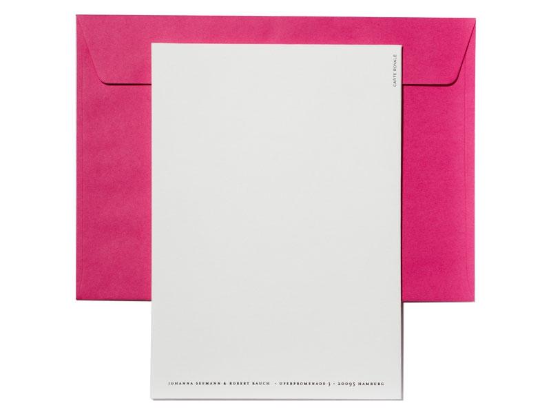 Hochzeitseinladung mit Blütenzweig und pinkem Briefumschlag.