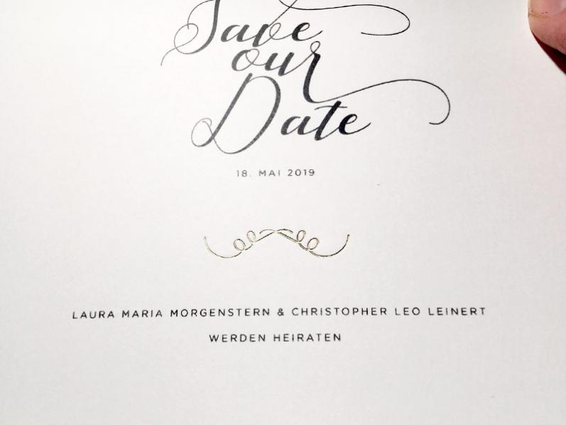 Kalligrafie Save-the-Date Karten gedruckt auf quadratischem Büttenpapier mit gold geprägtem Ornament.