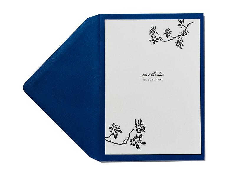Save-the-Date Karte mit Blütenzweigen und poetischer Schrift.