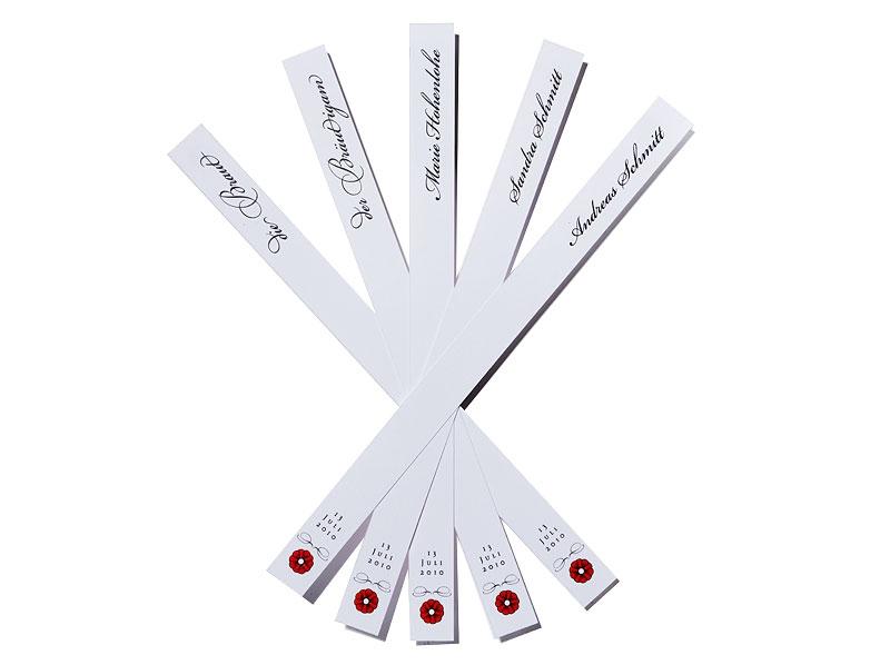 Personalisierte Tischkarten im schmalen Format mit Ornament und kleiner Blüte.
